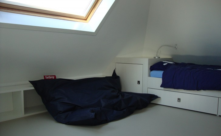 Op maat gemaakte bed met kastruimte onder het schuine dak