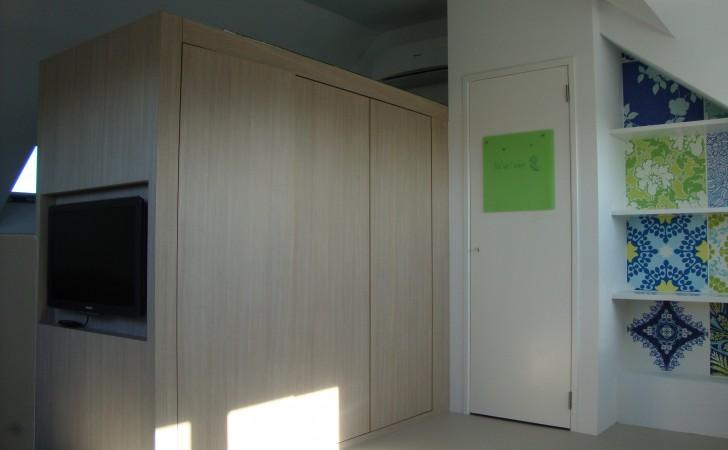 Kastenwand met tv als scheidingswand van kinderkamers op zolder