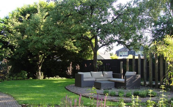 De zithoek is geplaatst op een ovaalvormig terras met langszij hoge robuuste eiken palen die het terras op een open manier afschermen. Grassen en weelderige beplanting tussen de palen zorgen voor een heerlijke ruis.