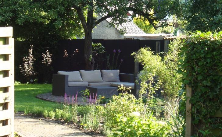 Het slingerpad van gras dat overgaat naar steen en de beide delen van de tuin verbindt.