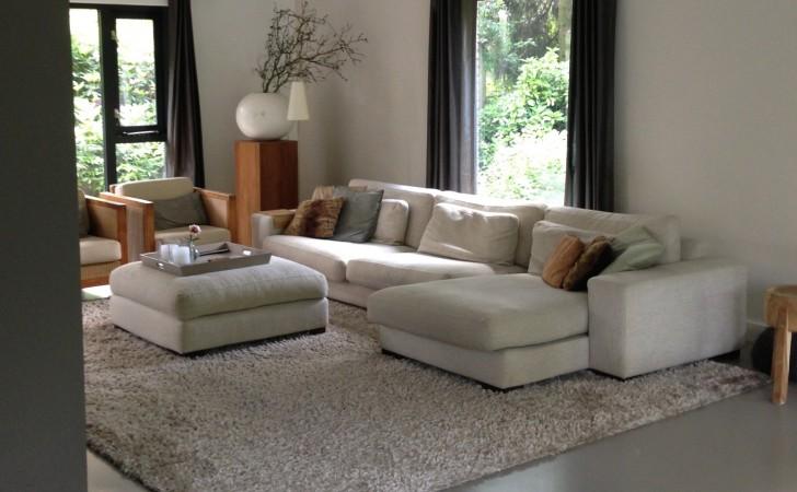 Heerlijke ruime loungehoek bij de openhaard. Een warme uitstraling door de aarde tinten van de meubels en gietvloer gecombineerd met accentkleuren en het grote warme carpet.